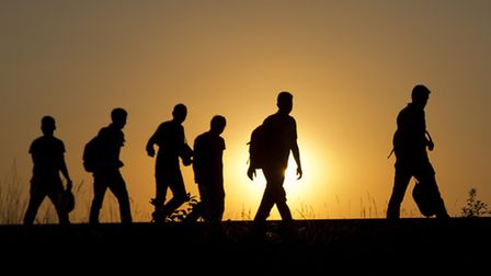 A group of refugees walk on the railway tracks after crossing from Serbia, in Roszke, Hungary. (AP P