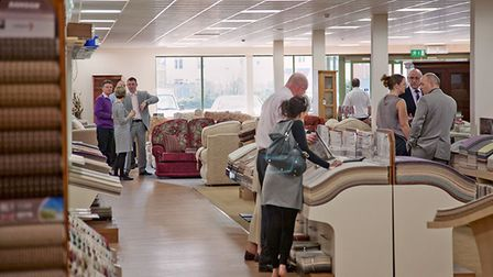 Photograph showing inside a busy carpet and flooring showroom with groups of people looking at samples