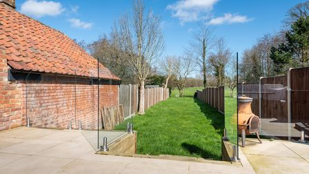 Photograph of a sunny bright garden with narrow lawn and a patio fenced off by glass balustrades