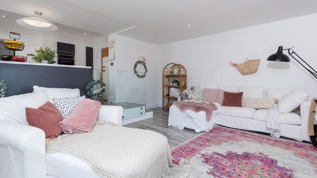 Photograph of a grey modern kitchen raised on a plinth and a neutrally decorated sitting room with pink accessories
