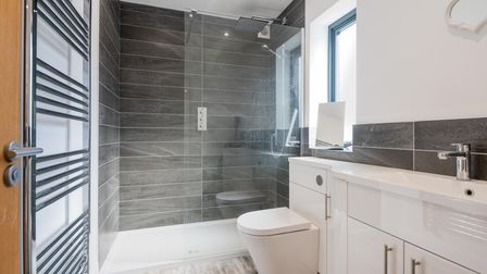 Photograph of a contemporary grey and white shower room with double-sized walk in shower cubicle