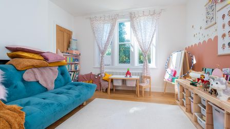 Photograph of a sun-kissed play room with modern bright blue sofa, rug over wood floors and wooden cupboards