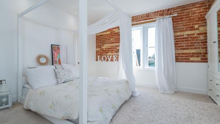 Photograph of a master bedroom with white four poster bed in front of a window and exposed brick wall