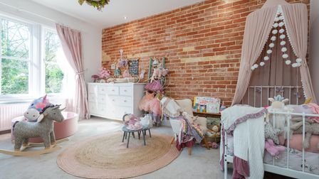 Photograph of a modern child's bedroom with exposed brick wall, carpeted floor and large window