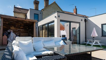 Photograph of an L-shaped seating area at the back of a modern house extension, bathed in sunshine