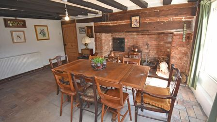 Photograph showing a dining room with large brick-built hearth, beamed ceiling and table and chairs to seat 8