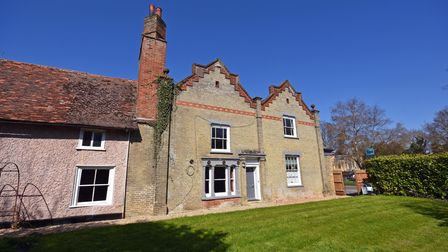 Exterior photograph of a brick-built farmhouse-style building with period details and a tall chimney with lawns in front