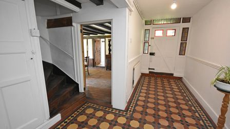 Photograph showing large entrance hall with wooden enclosed staircase leading up, and patterned tiled floor