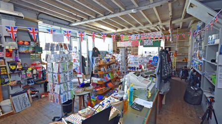 Photograph showing inside a gift shop with beamed ceilings, wooden floors and counters and shelving units