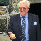 AN elderly man in a suit holding a yellow baby chick