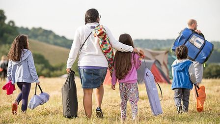 Family with camping equipment walking across a British field to pitch their tent