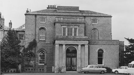 A grand looking hall with cars from the 1960s parked outside