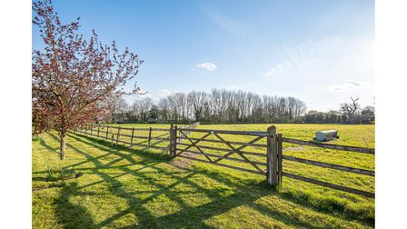 Lawns lead to a pond, post and rail fenced paddocks and a belt of mature woodland