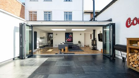 A building extension with bi-fold doors, inside is a sofa, dining table and chairs and a wood burner