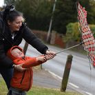 Three-year-old Cody Andrews battling with an umbrella with help from mum Leanna, as high winds hit N