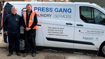Two men standing in front of a white van which says Press Gang Laundry Services on it