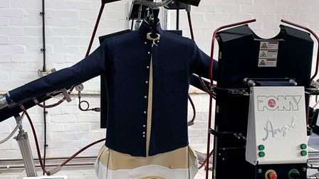 A dark coloured shirt on a piece of laundry equipment