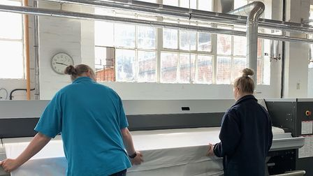 Two women using a roller ironer to press a sheet