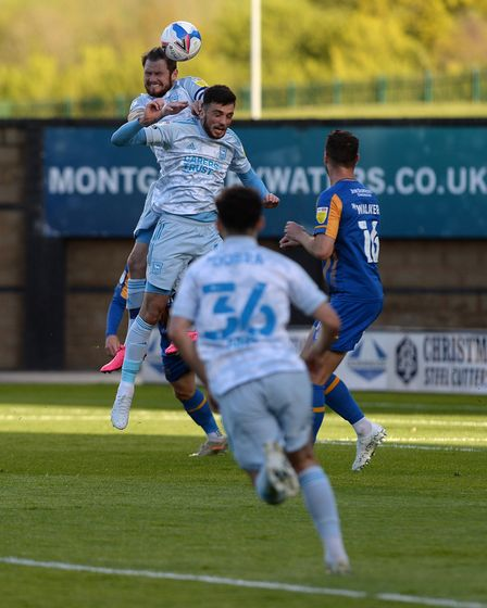James Norwood climbs highest to head wide at Shrewsbury Town.