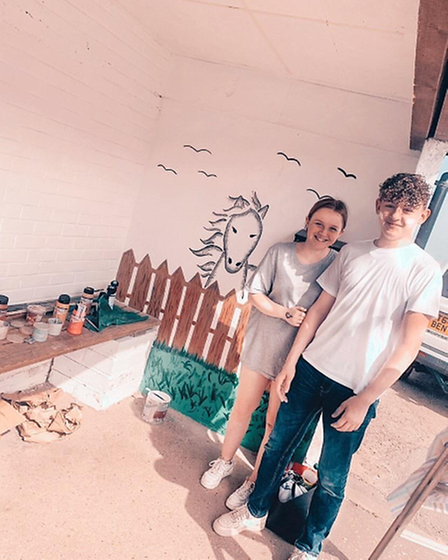A group of teenagers have transformed a drab bus shelter in North Norfolk with a colourful mural featuring their village.