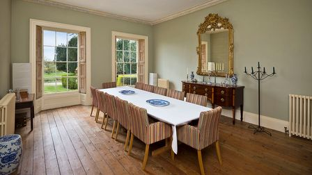 Period-style dining room with high ceiling, wood floors and a ten-seater dining table with striped chairs