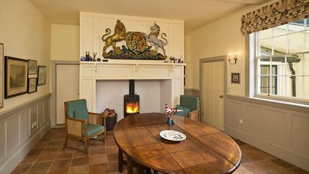Large reception room with feature fireplace with inset woodburner, tiled floor and oval-shaped wooden table