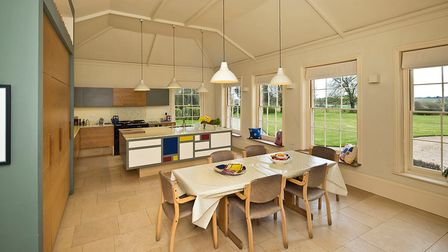 Large kitchen/diner with partly vaulted roof, kitchen island with Cubist tiling and low hanging lights over a table