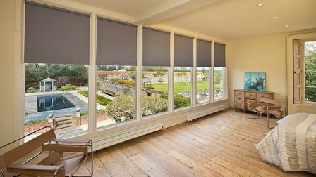Large light-filled double bedroom, lots of windows, wooden floors, overlooking neat walled garden with pool