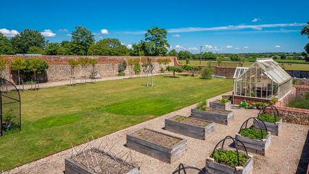 Neat raised beds set on to a gravel area next to bright green lawn surrounded by traditional high garden walls