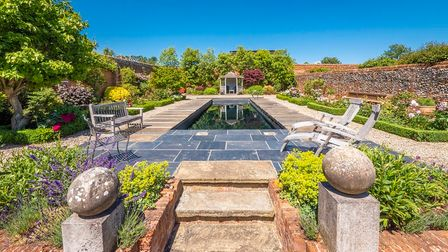 Walled garden with narrow natural-looking heated swimming pool surrounded by paved terrace and steps
