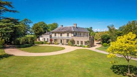 Large Georgian country house with sweeping circular driveway set behind lawns under bright blue sky