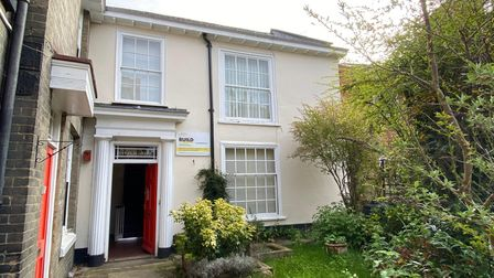 Corner end terrace property with white sash windows, cream-coloured paintwork and a red door with garden