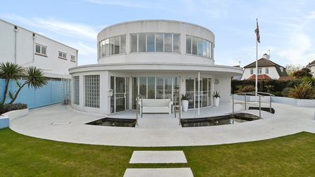 Circular modernist white home with floor-to-ceiling windows under bright blue sky