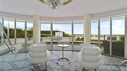 Two chairs overlooking panoramic view of the sea through floor-to-ceiling floored windows