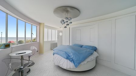 Circular double bed in a curved bedroom with long panoramic windows