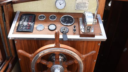 The helm of the refurbished 60-year-old wooden Broads cruiser, Noisy Goose