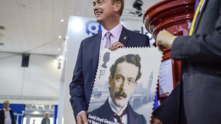 Leader of the Liberal Democrats, Tim Farron holds a stamp featuring David Lloyd George during his wa