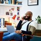 Man in his 30s sitting on chair with laptop, on phone call, communication, owner, entrepreneur