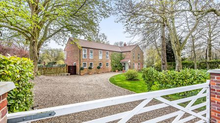 Large modern country house with huge gravel sweeping drive lawned gardens and trees with a gate