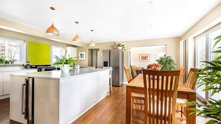 Modern white and green kitchen with glossy island, oak table and six chairs, open-plan space