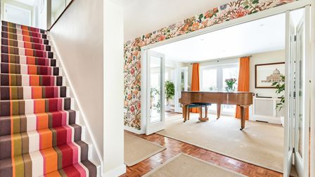Floral wallpaper over bifold doors opening into a piano room, striped stairs leading up, oak entrance hall floor