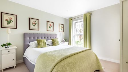 Pale green double bedroom with white double bed, green curtains, bedspread, side table and floral paintings