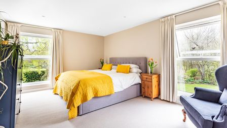 Double bed against wall of a spacious bedroom with bright yellow linen and two windows overlooking gardens