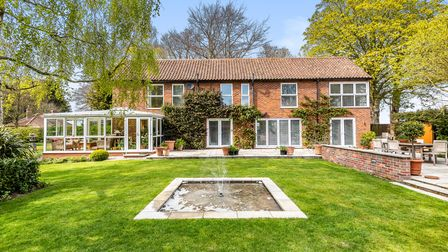 Large brick-built family home with conservatory overlooking rear garden with lawns and water feature