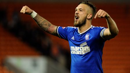 Luke Chambers celebrates with the fans at Blackpool