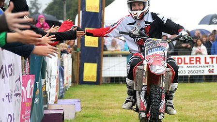 Aylsham Show 2014 action. A Bolddog Lings Motorcycle Freestyle Display Team rider greets the crowd.
