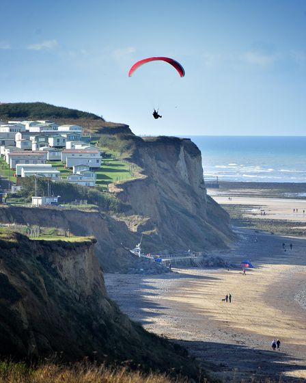 A paraglider flying past the cliffs and holiday parks at East Runton. Picture: ANTONY KELLY