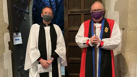 Two priests stand side-by-side, one in white (Revd Warmington, left), one in red robes.