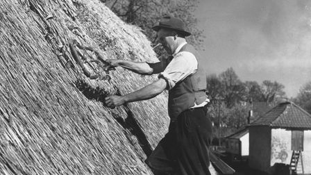Saxlingham thatcher working on the roof of the old school at Saxlingham Nethergate in 1953.