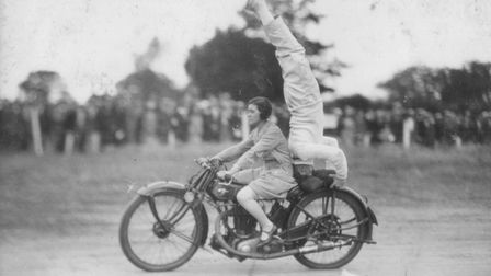 Tricky Newman does a headstand on his motorbike, while his partner drives.